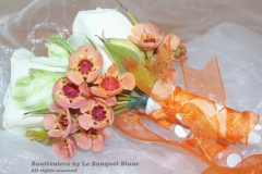 orange wax bouttoniere with spray roses